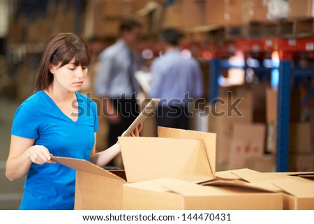 Worker In Warehouse Checking Boxes Using Digital Tablet