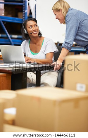 Worker In Warehouse Wearing Headset And Using Laptop - stock photo