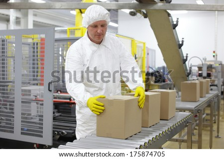 worker in white apron dealing with boxes at packing line in factory - stock photo