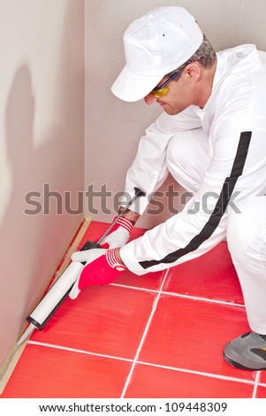 worker in white clouts lays silicone sealant corner wall floor - stock photo