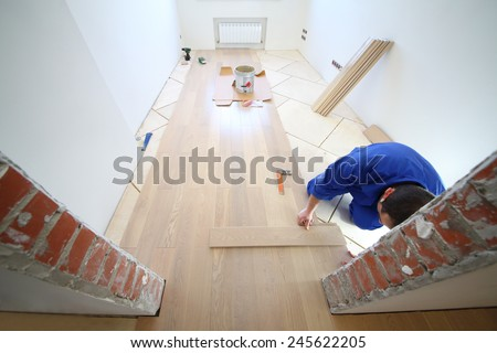 Worker  in white room where the laminate is laid, view through doorway - stock photo