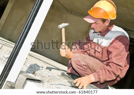 worker in work uniform hammering a screw in concrete - stock photo