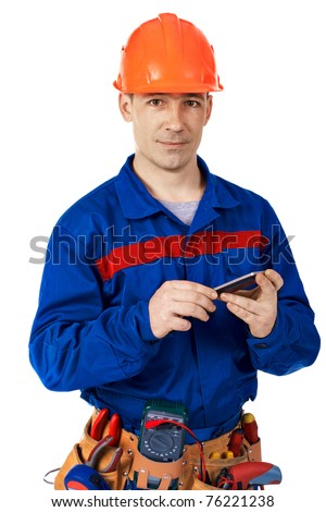 Worker in work-wear with modern mobile phone against white - stock photo