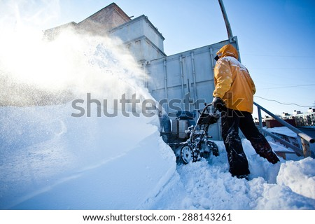 Worker in yellow winter jacket removes snow near his garage with a snow throwing machine at a sunny winter day. Clouds of snow dust around. Seasonal photo - stock photo