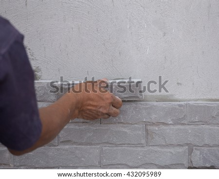 worker install stone wall tile with cement for house decoration