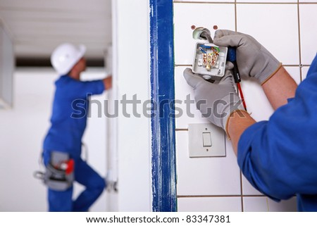 Worker installing a plug - stock photo
