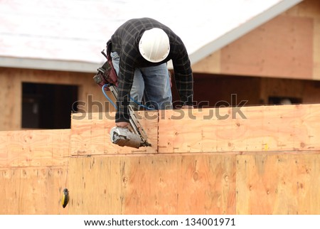 Worker installing a second floor wood joist at a large commercial housing development in Oregon - stock photo