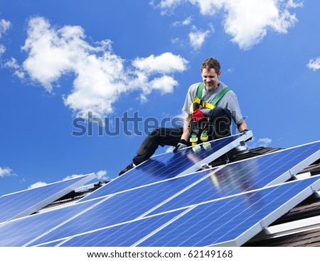 Worker installing alternative energy photovoltaic solar panels on roof - stock photo