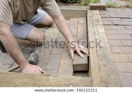 Worker Installing Brick Pavers - stock photo