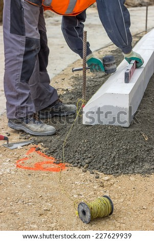worker installing concrete curb stone and using string with metal stakes to level at sidewalk construction site. Selective focus. - stock photo