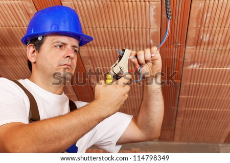 Worker installing electrical wiring in a new building - working on the ceiling wires - stock photo