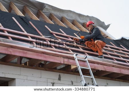 Worker installs bearing laths on the truss system - stock photo