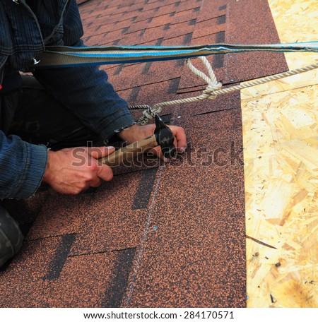 Worker installs bitumen roof shingles - closeup on hands - stock photo