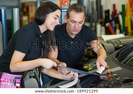 Worker instructing female apprentice in car wrapping workshop - stock photo
