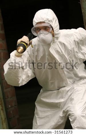 worker investigates a crime scene with lamp - stock photo