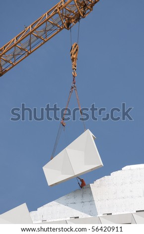 Worker is assisting the placing of a hoisted concrete facade element