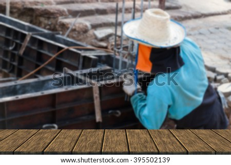 worker is constructing underground floor of the building (blur background with wood table top for display or montage your product)