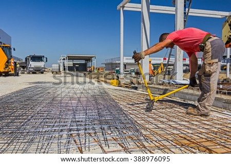 Worker is cutting reinforcement mesh with bolt cutters at building site. - stock photo