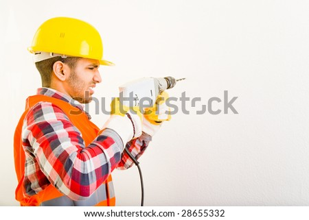 Worker is drilling a hole in a wall - stock photo