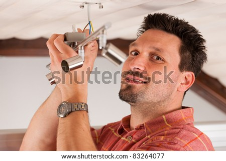 Worker is installing a luster in a house on the ceiling - stock photo