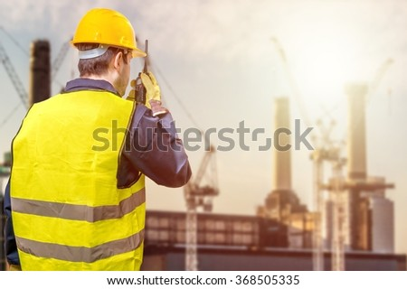 Worker is using radio and crane site during sunset. Construction concept. - stock photo