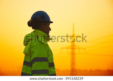 Worker is watching electricity pylons and substation at the sunset - stock photo