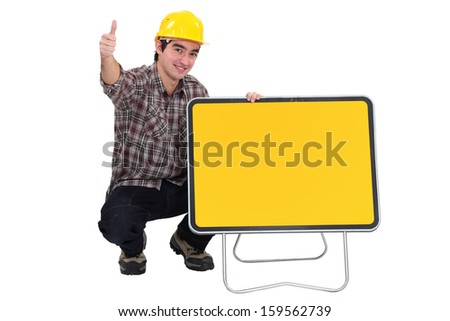 Worker kneeling by road sign - stock photo