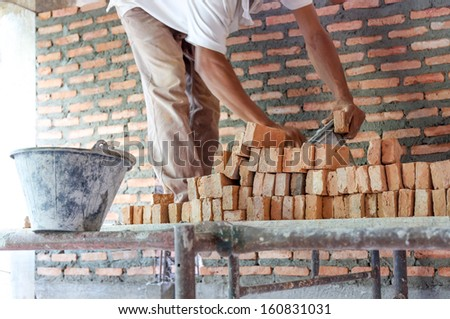 Worker laying bricks to build house wall in a construction site - stock photo