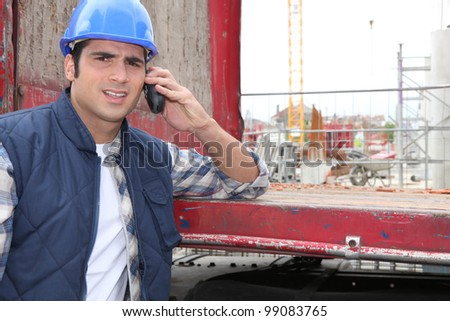 Worker leaning on red beam - stock photo