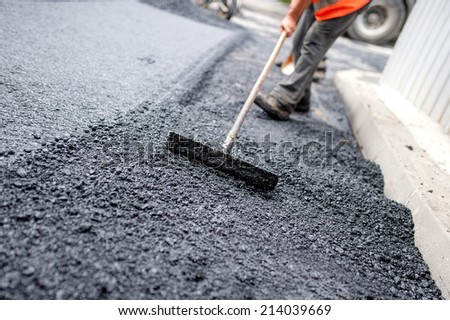 Worker leveling fresh asphalt on a road construction site, industrial buildings and teamwork