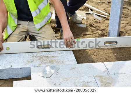 Worker levels installed paving with a spirit level. Installation of granite paver blocks series. - stock photo