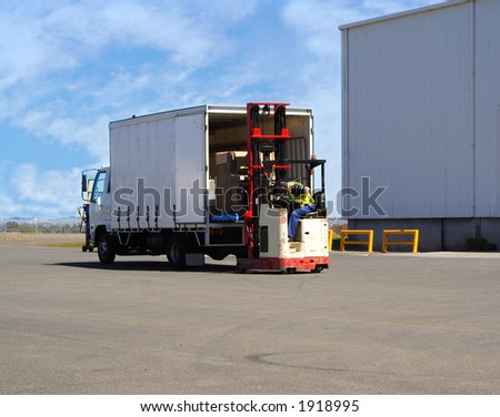 Worker loading truck on forklift - stock photo