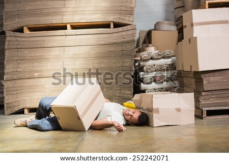 Worker lying on the floor in warehouse - stock photo