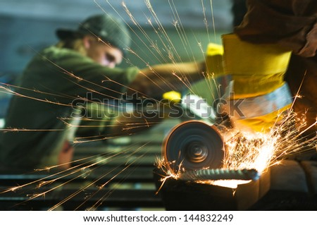 Worker making sparks while welding steel - stock photo
