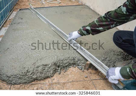 Worker making the level of the concrete slab.