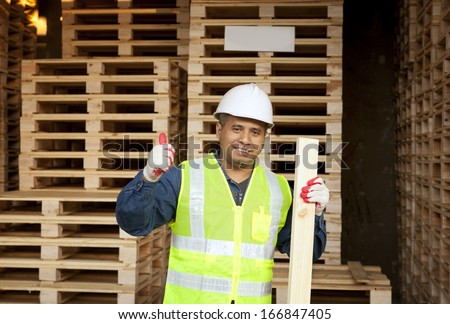 Worker man holding timber with giving thumb up