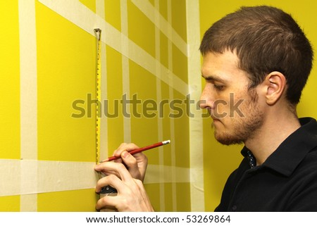 worker man measuring interior wall with masking tape - stock photo