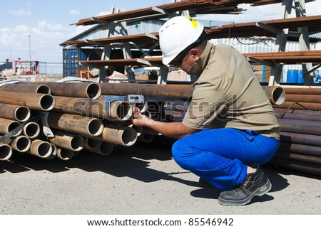 worker measures the pipes - stock photo