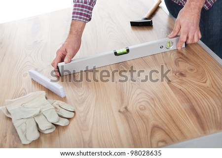 Worker measuring leveling of a laminate floor