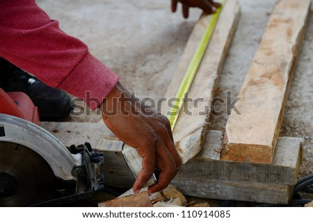Worker measuring the length of wood.