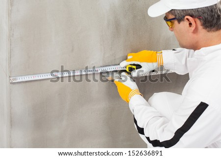 Worker measuring the level of a lath - stock photo