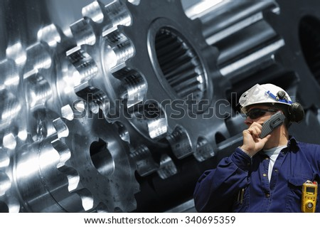 worker, mechanic with machine-parts, cogwheels in background - stock photo