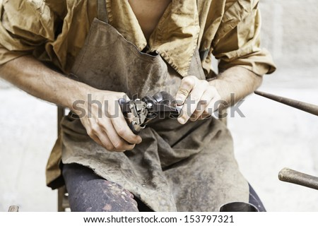 Worker metal craftsman, an artisan detail, tradition and old work - stock photo