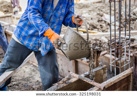worker mixing cement mortar plaster for construction - stock photo