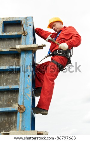 worker mounter assembling concrete formwork with hammer at construction site - stock photo