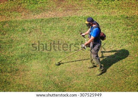 Worker mowing grass with trimmer mower. - stock photo