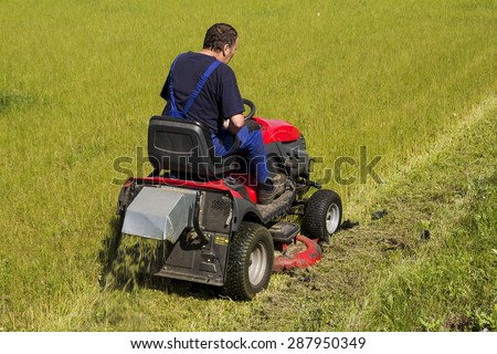 worker mows the lawn tractor - stock photo