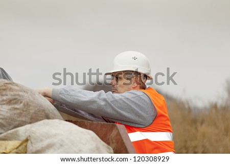 Worker near the garbage container - stock photo