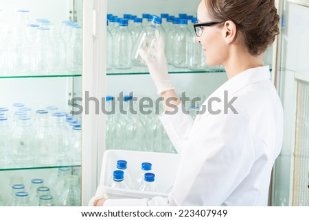 Worker of laboratory putting empty bottle into case - stock photo