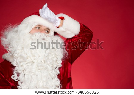 Worker of the Year. Tired Father Christmas wipes his forehead with his hand looking exhausted towards blank copyspace - stock photo